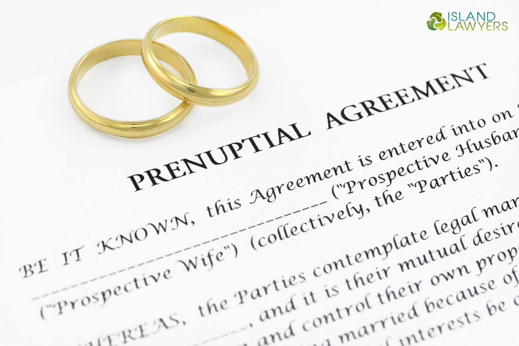 Wedding rings pictured over a prenuptial agreement